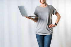 Young woman, dressed in gray t-shirt and blue jeans, standing on light gray background and holding laptop. Stock Image
