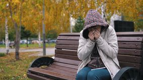 A young woman dressed in a hoody sneezes and blows her nose in the autumn park. stock video footage