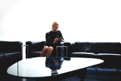 Young woman dressed in leather jacket writing text message on her mobile phone while waiting for meeting in office interior, Royalty Free Stock Image