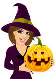 Young woman dressed like witch wearing dark clothing and holding a pumpkin in hand Royalty Free Stock Image