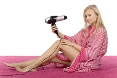 Young woman dressed pink/white bathrobe using hair drier royalty free stock image