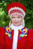 Young woman is dressed in the Russian national dress in summer p Royalty Free Stock Images