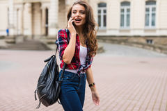 Young woman dressed in sportswear with smart phone traveling in the old city center Stock Photos