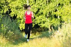 Young woman dressed sportwear jogging at summer park Royalty Free Stock Photo