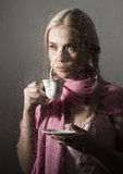 Young woman dressed in sweater drinking coffee or tea, posing behind transparent glass covered by water drops Royalty Free Stock Photos