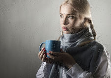 Young woman dressed in sweater drinking coffee or tea, posing behind transparent glass covered by water drops Stock Photo