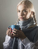 Young woman dressed in sweater drinking coffee or tea, posing behind transparent glass covered by water drops Royalty Free Stock Image