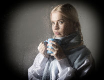 Young woman dressed in sweater drinking coffee or tea, posing behind transparent glass covered by water drops stock photography