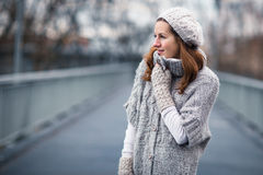 Young woman dressed in a warm woolen cardigan. Autumn/winter portrait: young woman dressed in a warm woolen cardigan posing outside in a city park Royalty Free Stock Photo