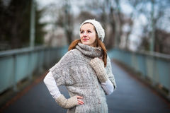 Young woman dressed in a warm woolen cardigan. Autumn/winter portrait: young woman dressed in a warm woolen cardigan posing outside in a city park Stock Photo