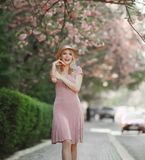 Young woman, dressed in white and yellow, in brimmed hat, stands among blossoming fruit trees and tries to reach out to. The branch with her hand stock photography