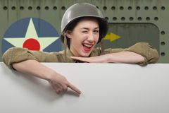 Young woman dressed in wwii military uniform with helmet showing empty blank signboard with copy space. Young woman dressed in wwii military uniform with helmet stock photography