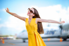 Young woman dressed in yellow dress simulating flight with hands Stock Image