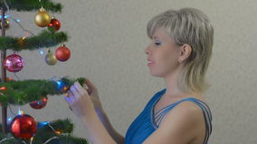 Young woman dresses the Christmas tree stock footage
