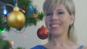 Young woman dresses the Christmas tree stock video footage
