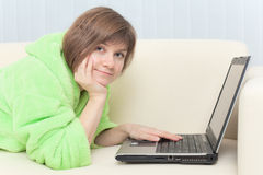 Young woman in dressing gown with laptop Stock Photos