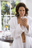 Young woman in dressing gown with mug in kitchen, portrait Royalty Free Stock Image