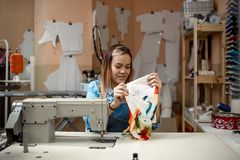 A young woman dressmaker holding a colored fabric royalty free stock images