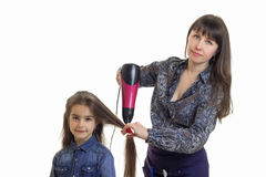 Young woman dries hair cute little girl isolated on white background Stock Photos
