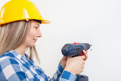 Young woman drilling a hole in the wall Stock Image