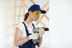 Young Woman Drilling Walls on Site Stock Photos