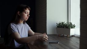 Young woman drink coffee at cafe, make sip and look to window stock footage