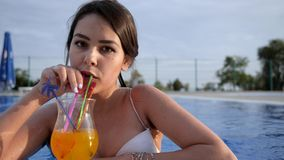 Young woman drink alcoholic beverage and Resting in Summer swimming pool on open air at holiday. Young woman drink colorful alcoholic beverage and Resting in stock video