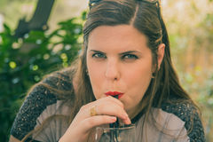 Young woman drink from a glass with drinking straw outdoor Stock Photo