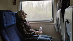 Young woman drink water while traveling by train stock video