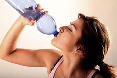 Young woman drinking. Out of a bottle after fitness stock photography