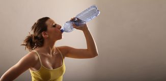 Young woman drinking. Out of a bottle after fitness royalty free stock photos