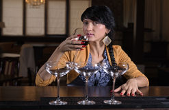 Young woman drinking alone at a bar Stock Image