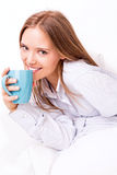 Young woman drinking in bed Stock Photos