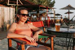 Young woman drinking beer in a beach bar. Enjoying sunset royalty free stock image