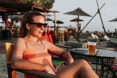 Young woman drinking beer in a beach bar. Enjoying sunset royalty free stock images
