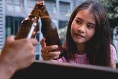 Young woman drinking beer. Party people enjoying summer day. Hap. Young woman drinking beer. Party people clanging bottles of beer together, enjoying summer day royalty free stock image