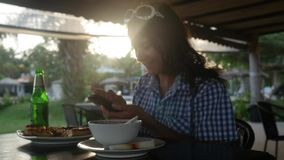 Young woman drinking beer and uses mobile phone in an outdoor cafe during sunset and lens flare effect. 3840x2160. 4k stock footage