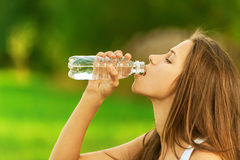 Young woman drinking bottle Stock Photography