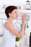 Young woman drinking a bottle of water in her kitchen Royalty Free Stock Images