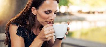 Young woman drinking cappuccino Royalty Free Stock Photos