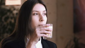 Young woman drinking cappuccino or tea with milk and smiling at camera. Business woman student, black jacket, white shirt, long hair brunette stock footage