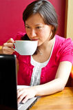 Young woman drinking cappuccino using her laptop Royalty Free Stock Image
