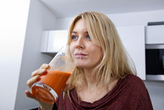 Young woman drinking carrot juice in kitchen Stock Photos