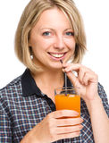 Young woman is drinking carrot juice Stock Photography