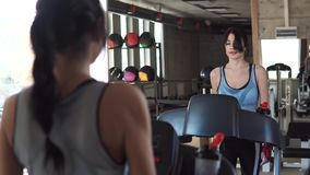 Young woman drinking clean water exercising in the gym. a girl walks on a treadmill. Girl running on the treadmill in the fitness room. young woman doing aerobic stock video footage