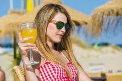 Young woman drinking a cocktail Stock Images