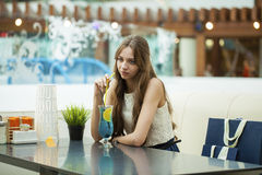Young woman drinking cocktail in a cafe Stock Image
