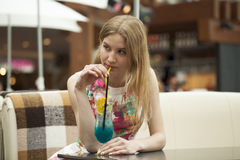 Young woman drinking cocktail in a cafe Stock Images