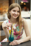 Young woman drinking cocktail in a cafe Stock Photography