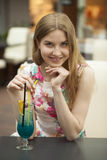 Young woman drinking cocktail in a cafe Royalty Free Stock Photo